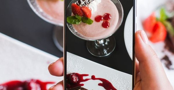 Hand holding a mobile phone taking a photo of pretty dessert on a table