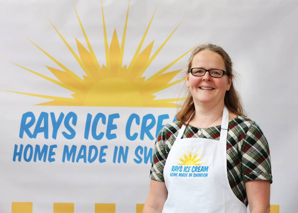Hadi Brooks, founder of Rays Ice Cream pictured wearing a Rays branded apron and standing in front of a Rays Ice Cream logo