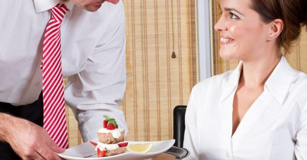 Man serving dessert to a lady sat at a restaurant table